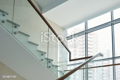 Part of staircase with railings and large window inside new contemporary business center or office building with many floors