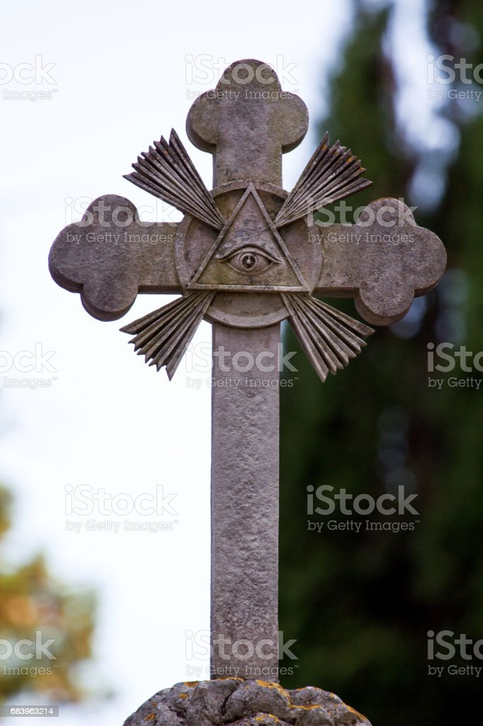 Part of stone cross with masonic motives on the grave, monument in cemetery, close up. Sculpture art. stock photo