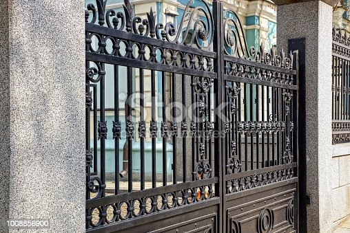 part of the black gate with a pattern of steel rods and concrete pillars