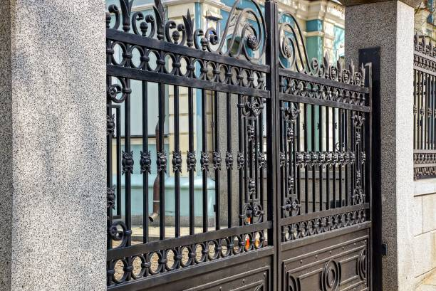 part of the black gate of steel bars and concrete pillars - portão imagens e fotografias de stock