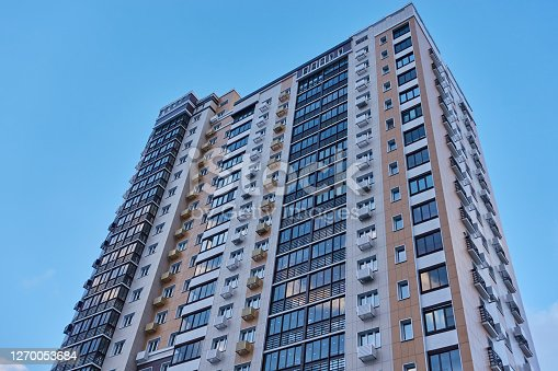 Part of the facade of a multi-storey residential building against the sky.