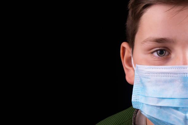 partie du visage d'un enfant dans un masque sur un fond noir. espace libre pour une inscription. - masque enfant photos et images de collection