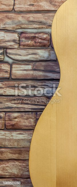 1014432572istockphoto Part of the guitar standing at the brick wall. Side view. 1069521250