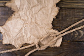 istock Part of the old burnt parchment and a knot of hemp rope lying on the table with a cork finish. Frame for your label. 903461628