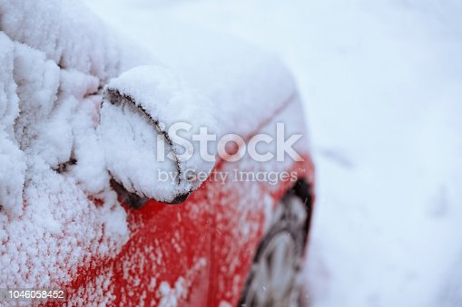 Part of the red car covered with snow. Mirror of the car