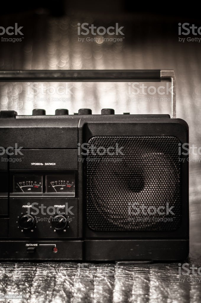 Part of the retro cassette tape recorder of the 80s with recording indicators with arrows and knobs on a sparkling background zbiór zdjęć royalty-free
