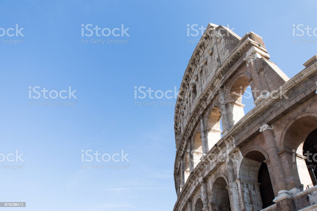 Part of the wall of Colosseum in Rome with cypress on background. stock photo