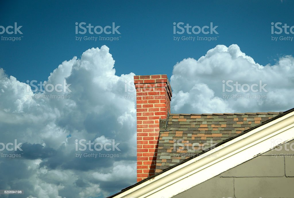 Part of tiled roof with brick chimney against clouds stock photo