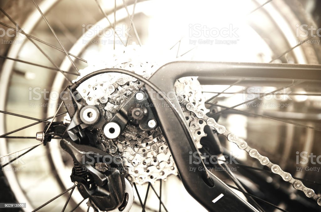 part of wheel and metal chain gear of black bicycle for sport competition background stock photo