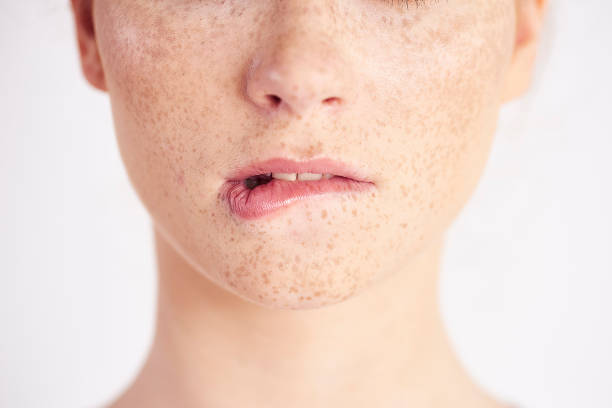 Part of woman biting her lip at studio shot stock photo