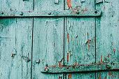 Part old green door. Old paint. Peeling paint. Part old green and red wood doors. Cracks.