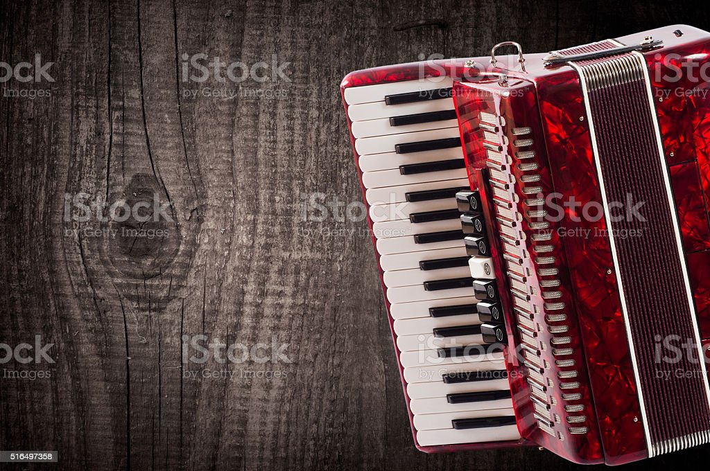 Part red accordion on wooden grey background. Write text stock photo