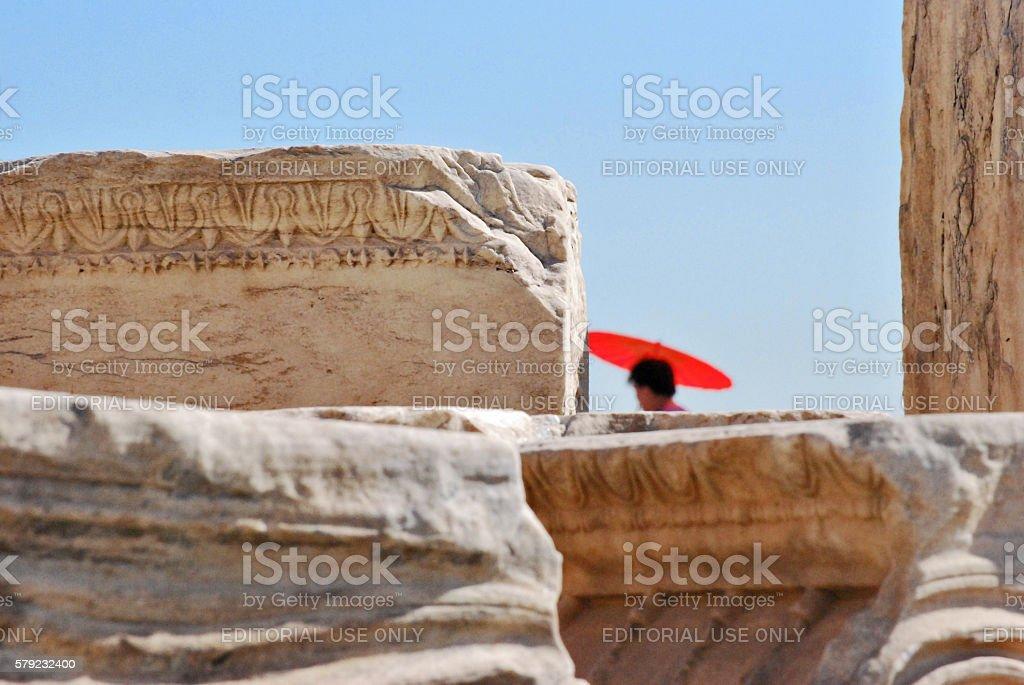 Parthenon ruins closeup with a red parasol stock photo