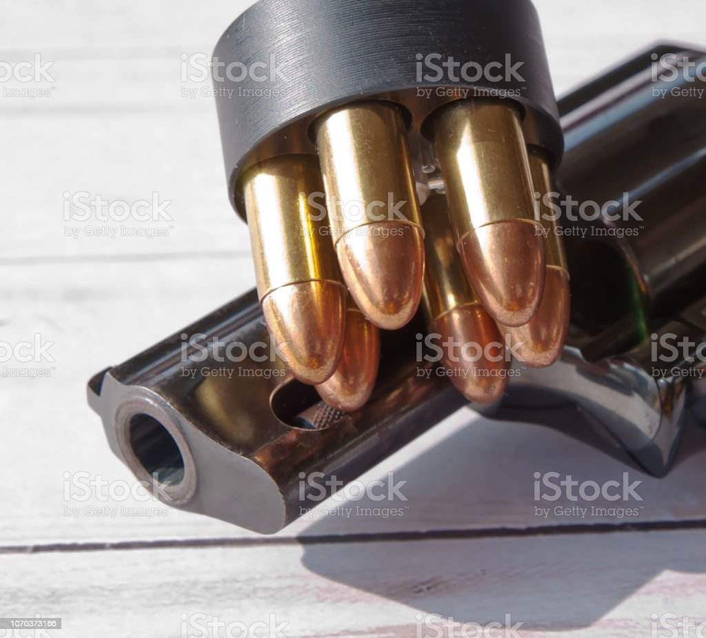 A partial black revolver shown on a wooden background with a speed loader on top if i stock photo