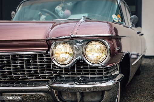 Close up of the front and grille of a  pink classic car from 1959 with lot of chrome and moldings and the head lights on