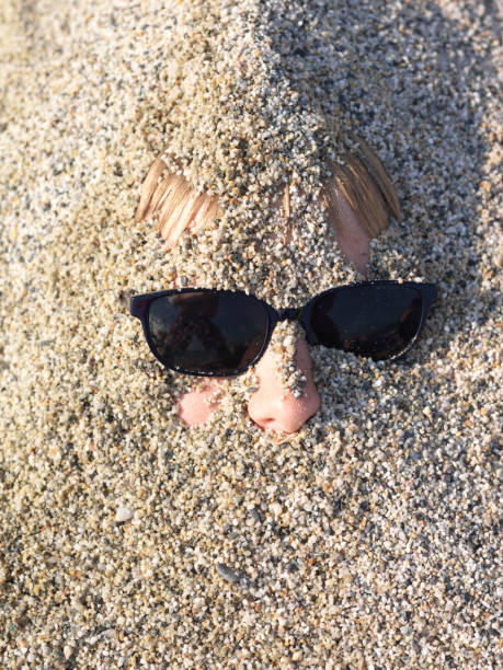Partial face of boy wearing sunglasses and covered in sand Directly overhead view head in the sand stock pictures, royalty-free photos & images