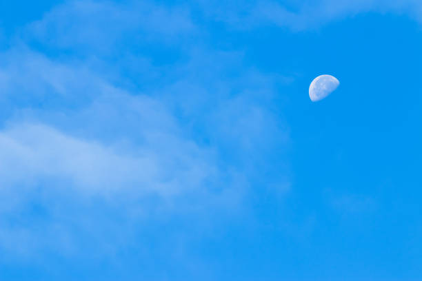 Partial moon against a blue morning sky stock photo