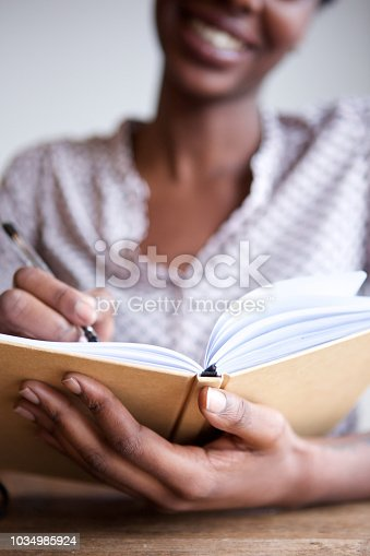 Close up partial portrait of smiling black female author at home writing in notebook