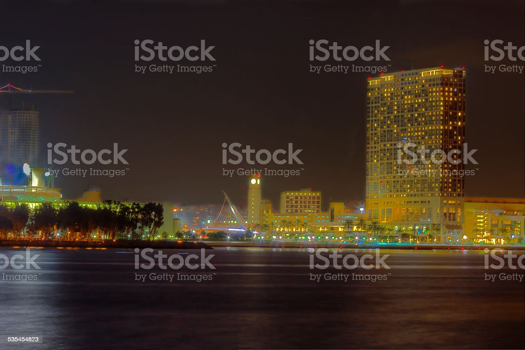 Partial San Diego skyline over water at night stock photo