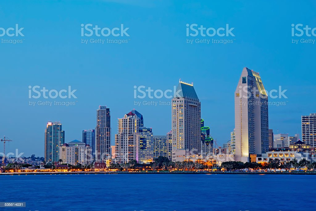 Partial skyline of San Diego over water at night stock photo