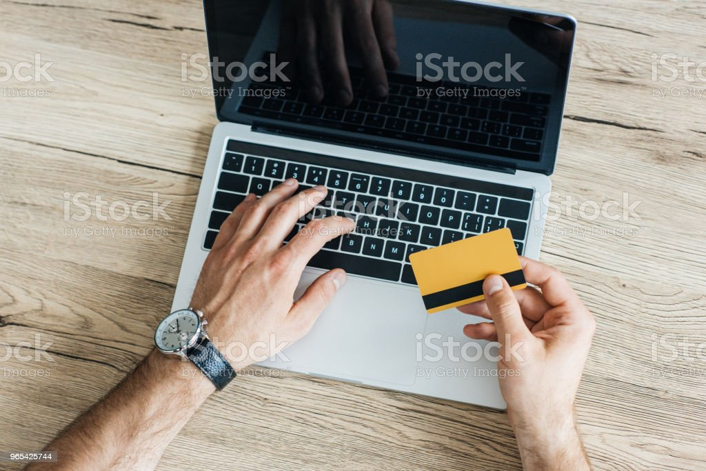 partial top view of person holding credit card and using laptop at workplace royalty-free stock photo