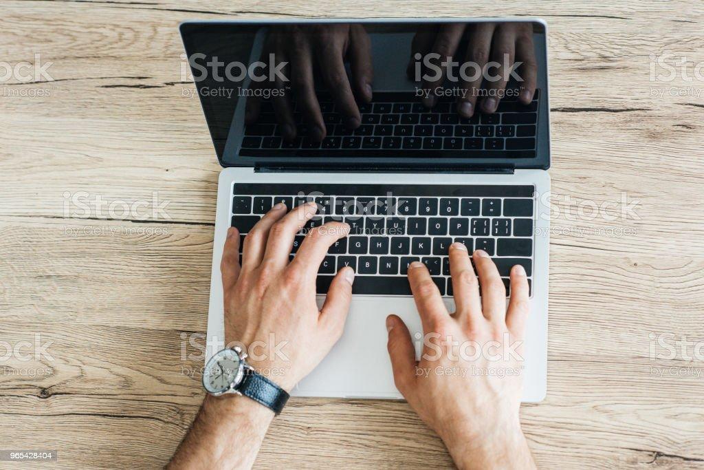 vista parcial de pessoa usando laptop com tela em branco na mesa de madeira por cima - Foto de stock de Computador royalty-free