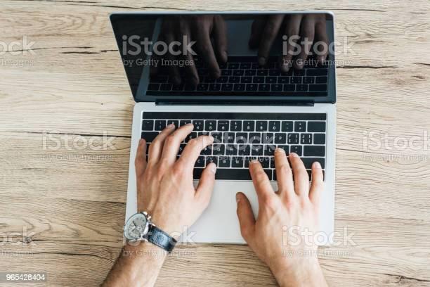 Foto de Vista Parcial De Pessoa Usando Laptop Com Tela Em Branco Na Mesa De Madeira Por Cima e mais fotos de stock de Computador