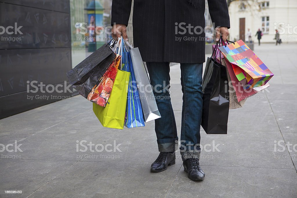 A partial view of a man in jeans carrying nine shopping bags royalty-free stock photo