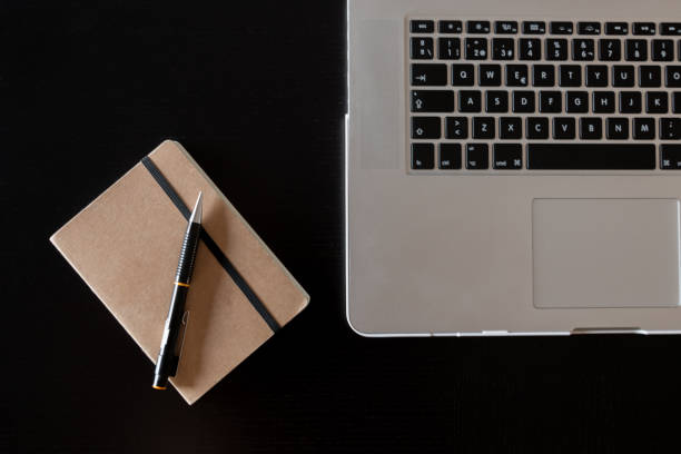 Partial view of a silver keyboard of a laptop and a notebook with a pencil on a dark wood desk stock photo