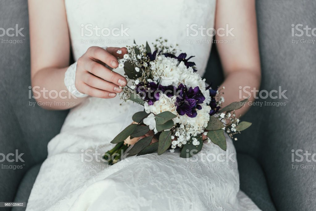 partial view of bride in white dress with beautiful bridal bouquet resting in armchair royalty-free stock photo