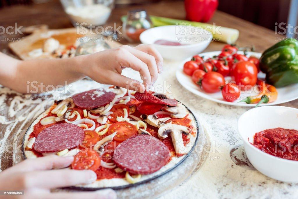 vue partielle de l'enfant, mettre les saucisses sur la pizza photo libre de droits