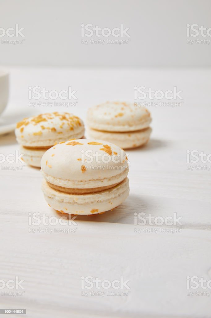 partial view of coffee cup and three macaroons on white wooden table royalty-free stock photo
