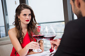 partial view of couple clinking glasses of red wine during romantic date in restaurant