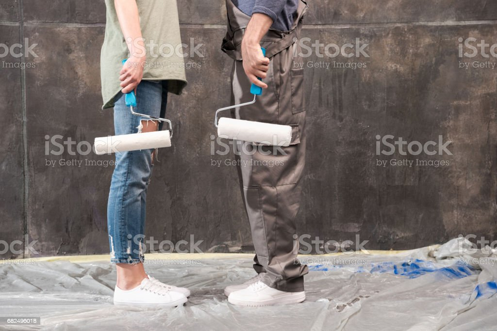 partial view of couple with paint rollers, renovation home concept Lizenzfreies stock-foto