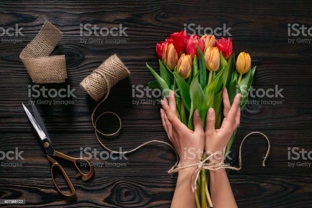partial view of female hands, rope, scissors and bouquet of flowers on wooden surface - Royalty-free Adult Stock Photo