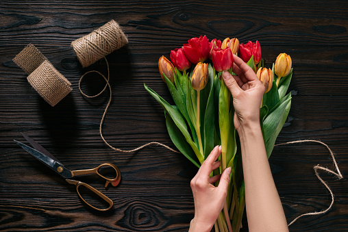 Partial View Of Female Hands Rope Scissors And Bouquet Of Flowers On Wooden Surface Stock Photo - Download Image Now