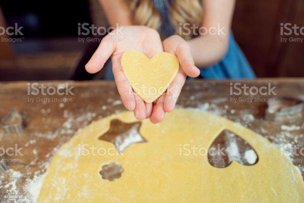 vue partielle de la fille tenant la pâte crue en forme de coeur pour cookie photo libre de droits
