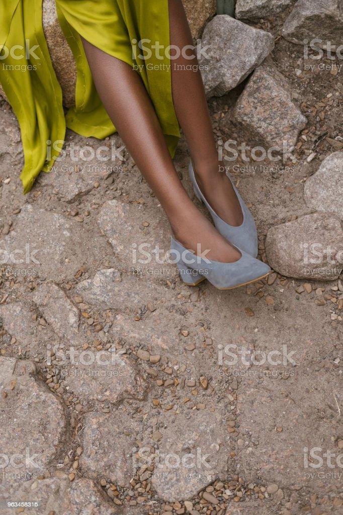 vista parcial de la chica de vestido amarillo y elegantes tacones gris en el pavimento - Foto de stock de A la moda libre de derechos