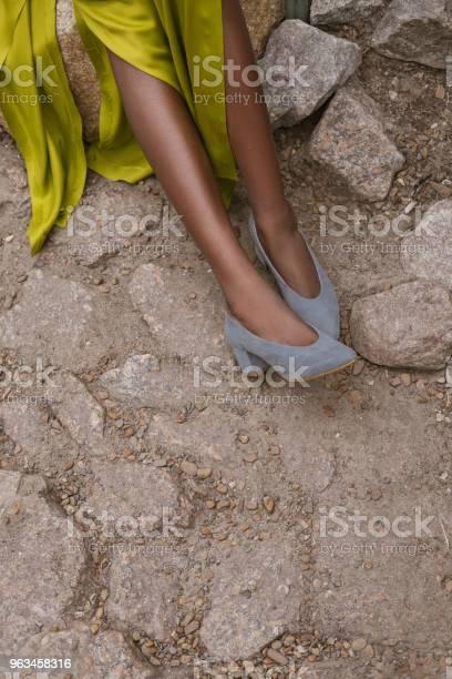Vista Parcial De La Chica De Vestido Amarillo Y Elegantes Tacones Gris En El Pavimento Foto de stock y más banco de imágenes de Calzado