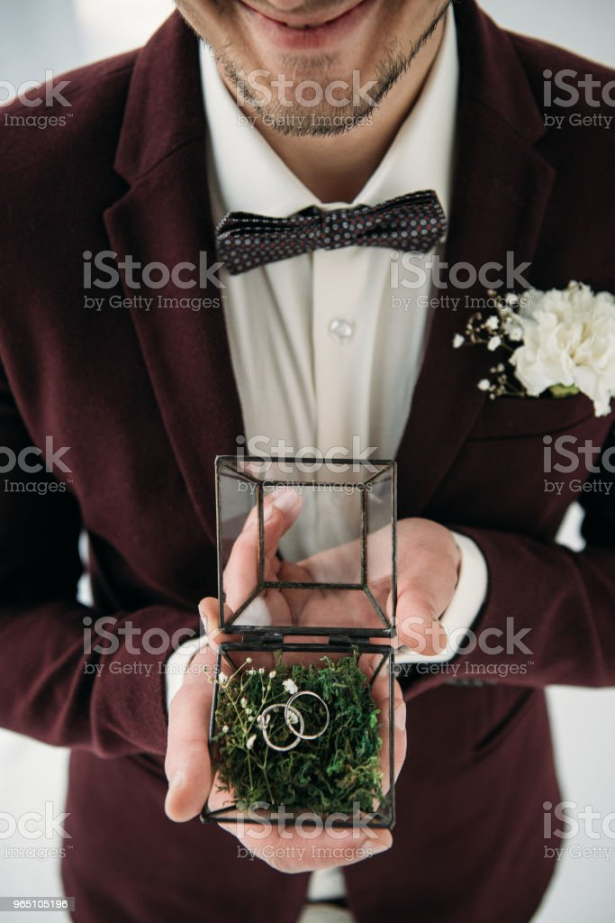 partial view of groom in suit with buttonhole and wedding rings in box in hands zbiór zdjęć royalty-free