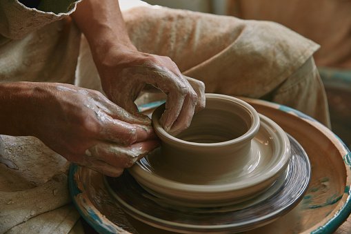 partial view of male craftsman working on potters wheel at pottery studio