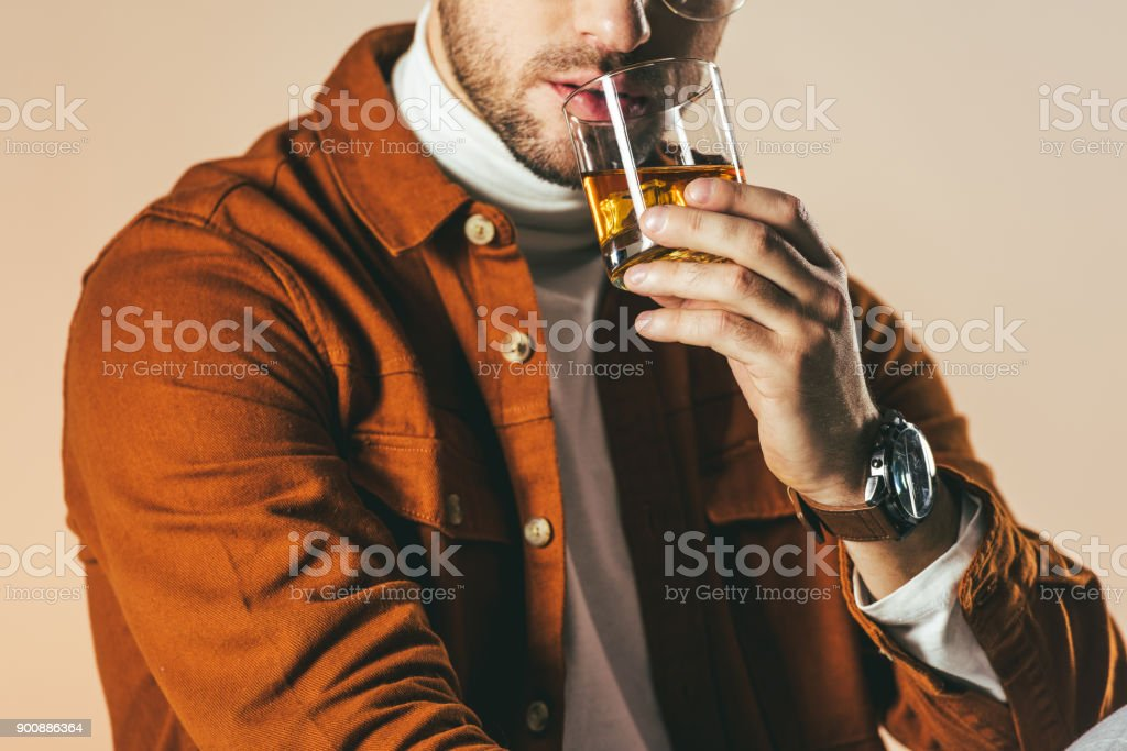 partial view of man in stylish clothing with glass of whiskey in hand isolated on beige stock photo