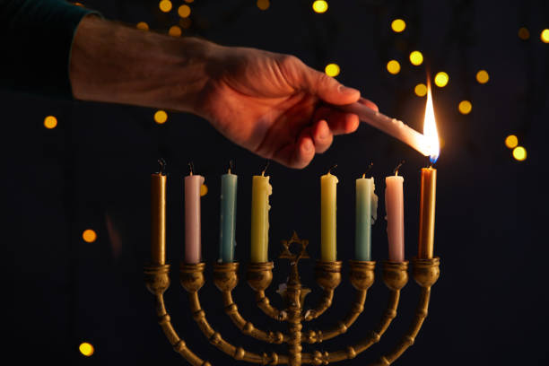 partial view of man lighting up candles in menorah on black background with bokeh lights on Hanukkah stock photo