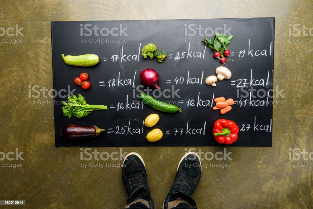 partial view of man standing near fresh vegetables and calories table, healthy lifestyle concept royalty-free stock photo