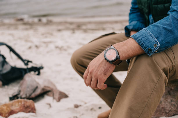 vista parcial del hombre con el reloj en la muñeca descansando en la playa - reloj de pulsera fotografías e imágenes de stock
