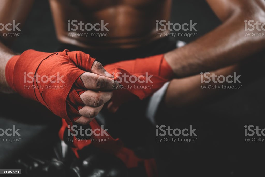 partial view of muay thai fighter swathign hand in boxing bandage stock photo