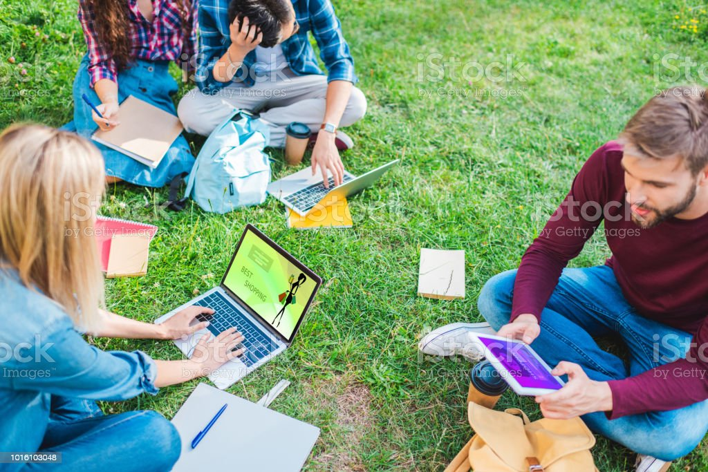 partial view of multiethnic students with notebooks and digital devices sitting on green grass in park stock photo