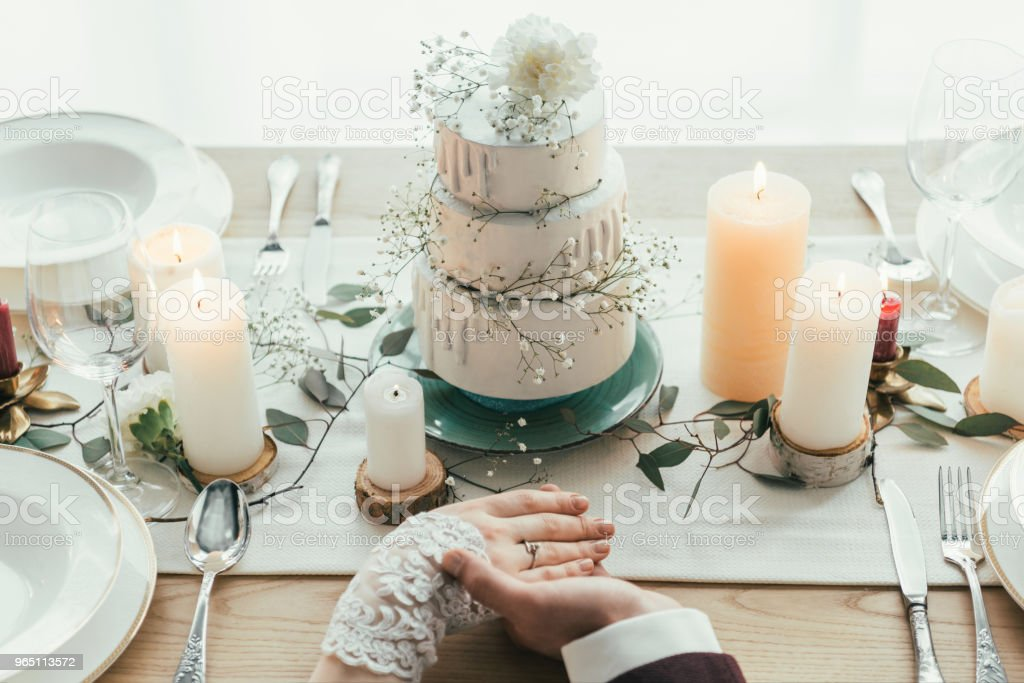 partial view of newlyweds holding hands while sitting at served table with wedding cake, rustic wedding concept royalty-free stock photo