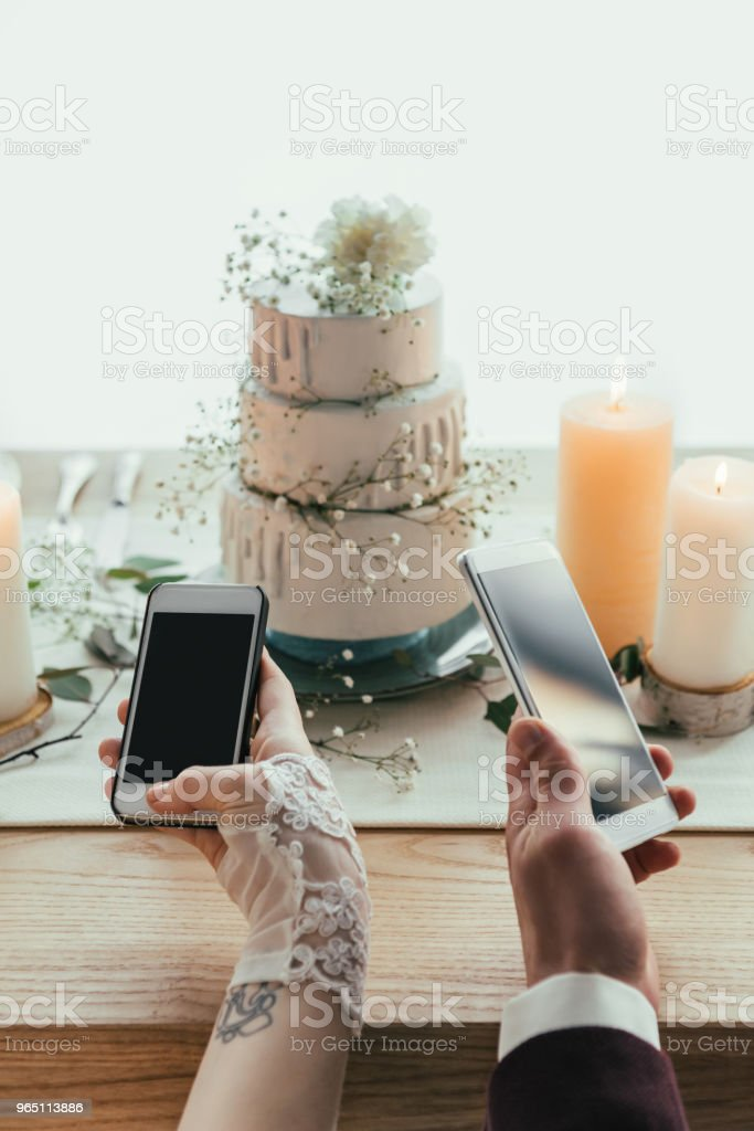 partial view of newlyweds using smartphones with blank screens while sitting at served table, rustic wedding concept zbiór zdjęć royalty-free