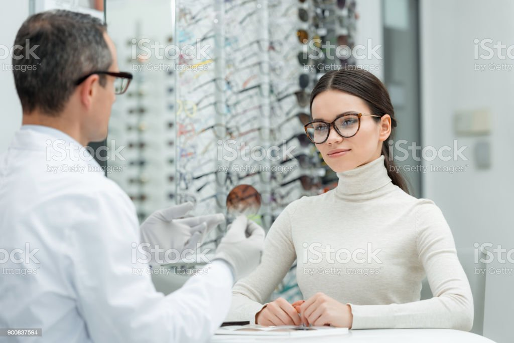 partial view of optometrist showing lens to patient in optics stock photo